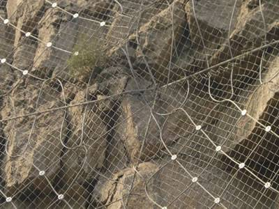 The galvanized wire rope net and chain link fence is covering the mountain.
