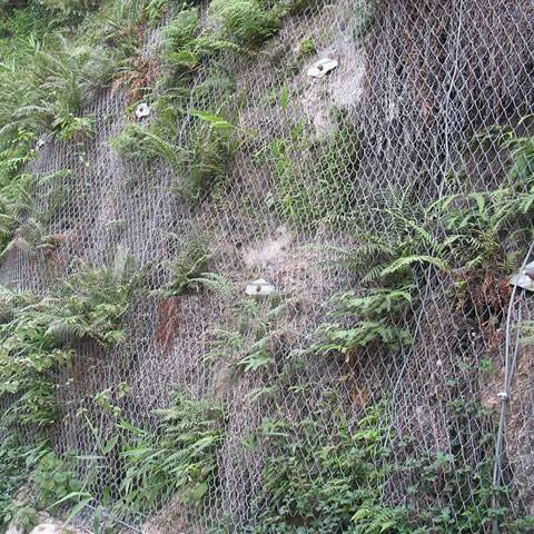 Hexagonal wire mesh is covering the mountain besides of the culvert.