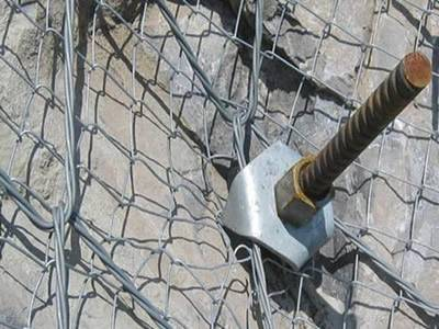 A prestressed anchor and anchor plate are fastening the spider spiral rope mesh.