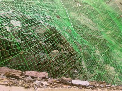The PVC coated wire rope net and chain link fence is covering the stone mountain.